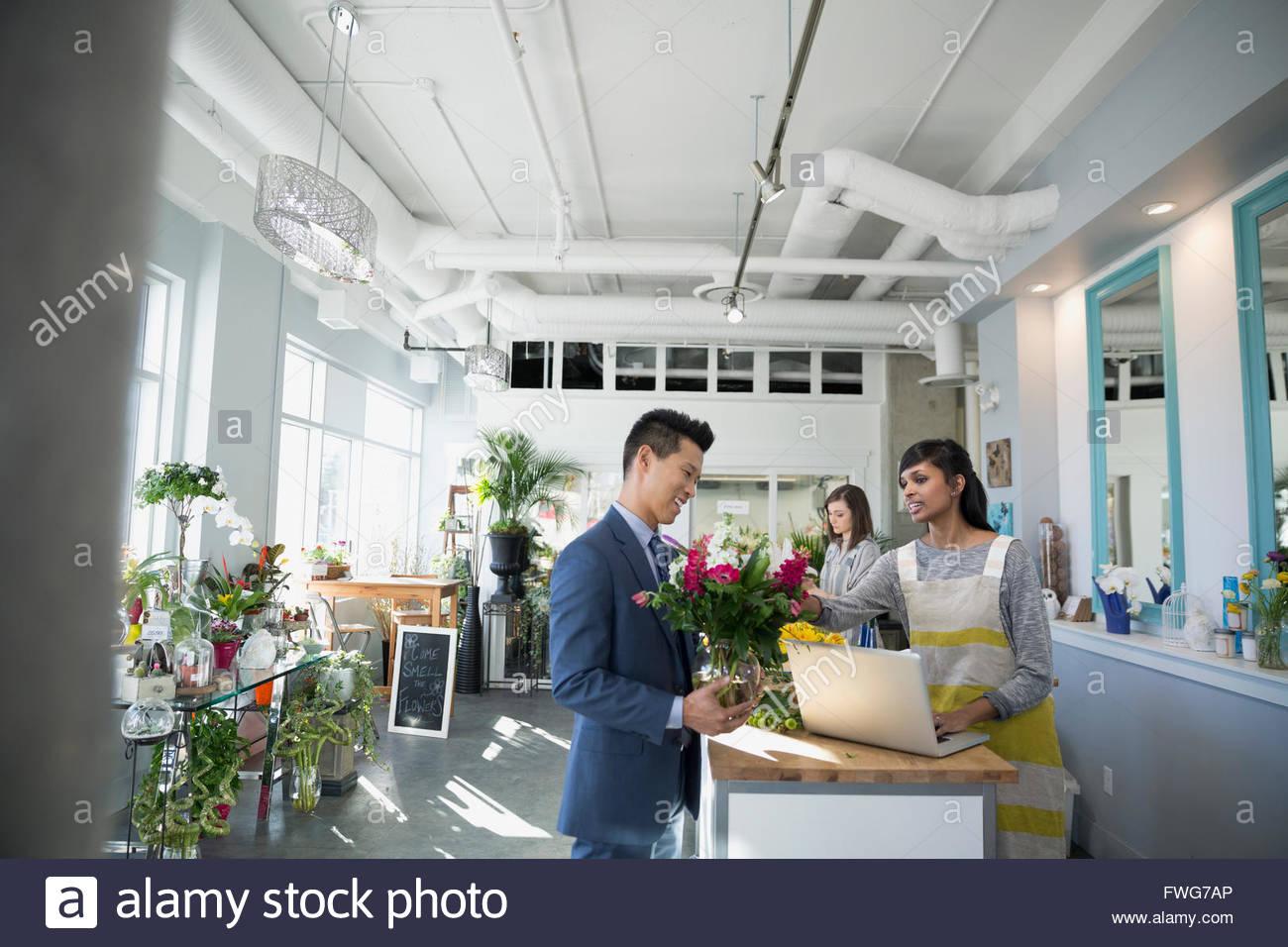Cliente che acquista bouquet nel negozio di fiori Immagini Stock