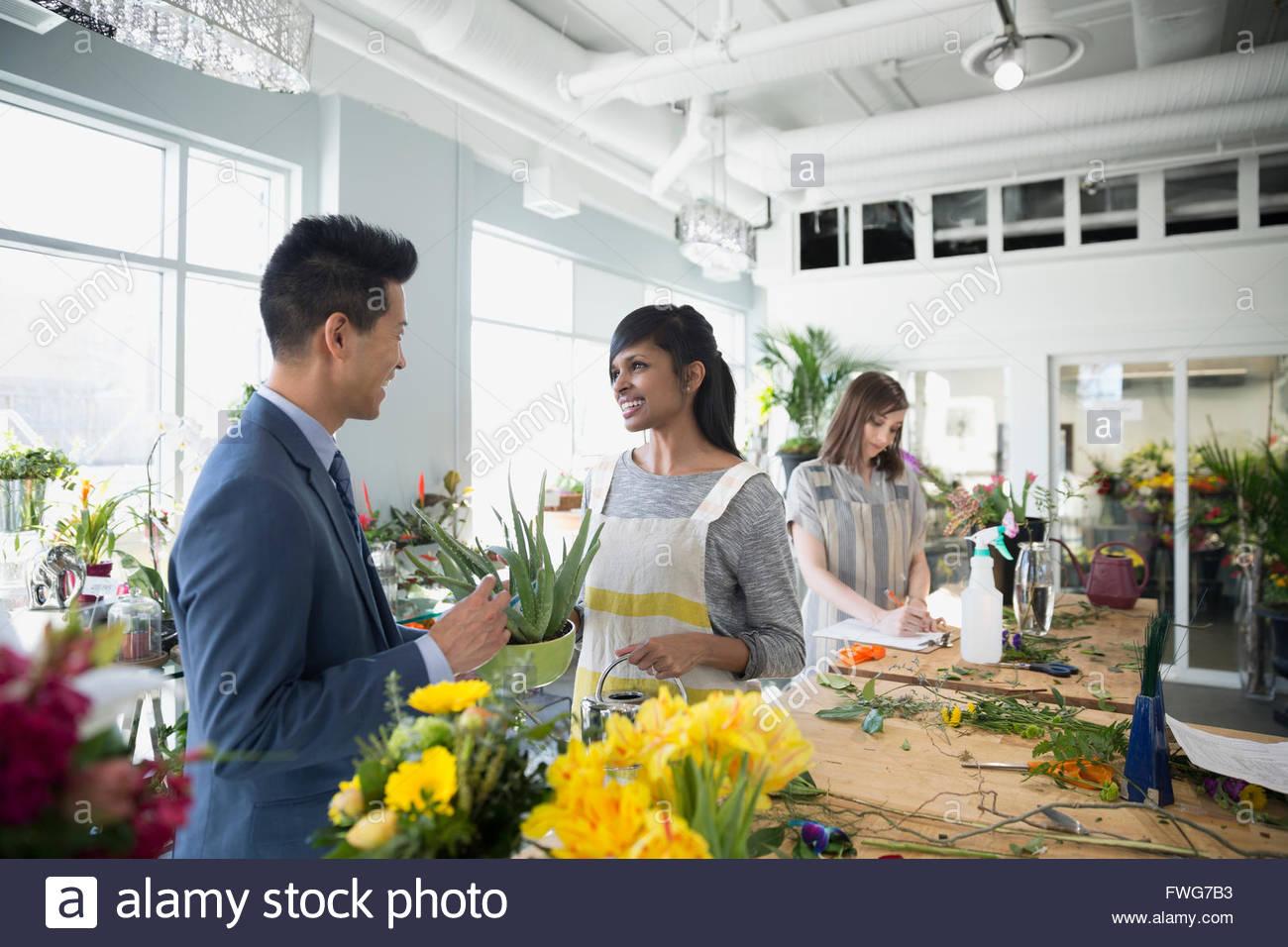 Fioraio aiutando il cliente nel negozio di fiori Immagini Stock