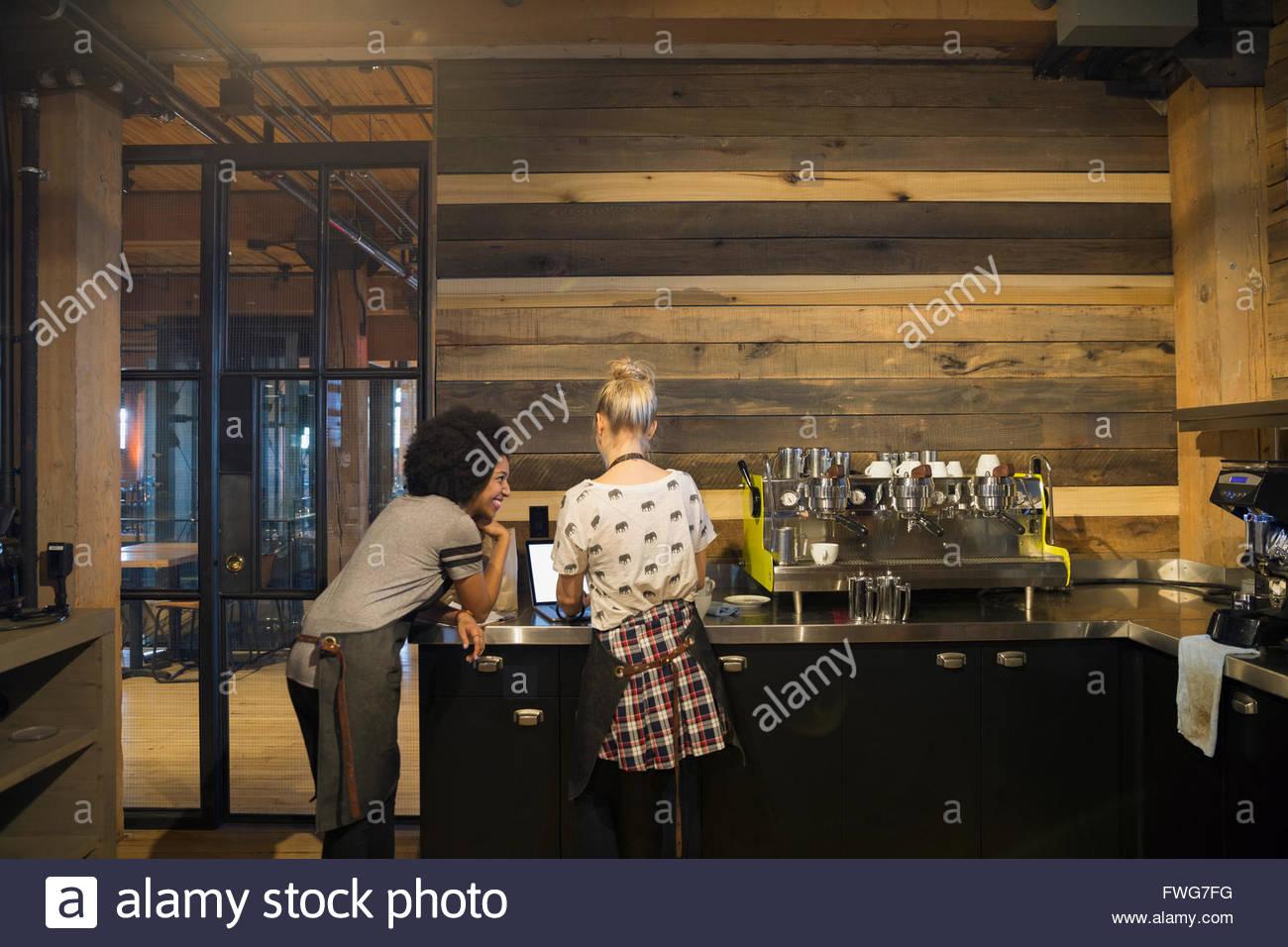 Baristi utilizzando laptop in coffee shop Immagini Stock