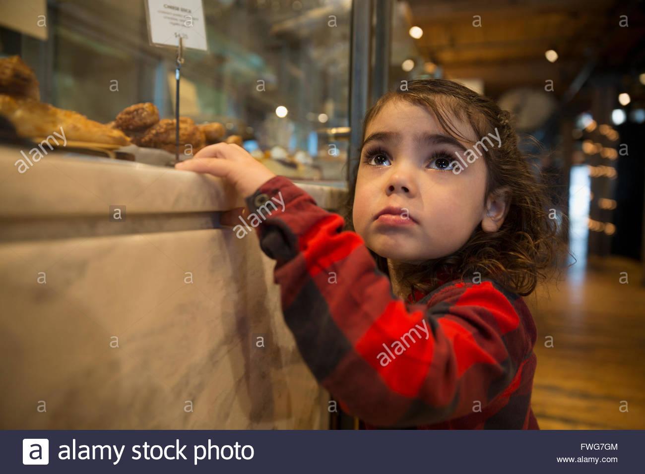 Ragazza carina guardando il panificio vetrina Foto Stock