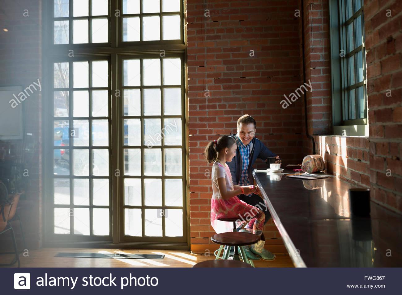Padre e figlia godendo di caffè nella caffetteria Immagini Stock