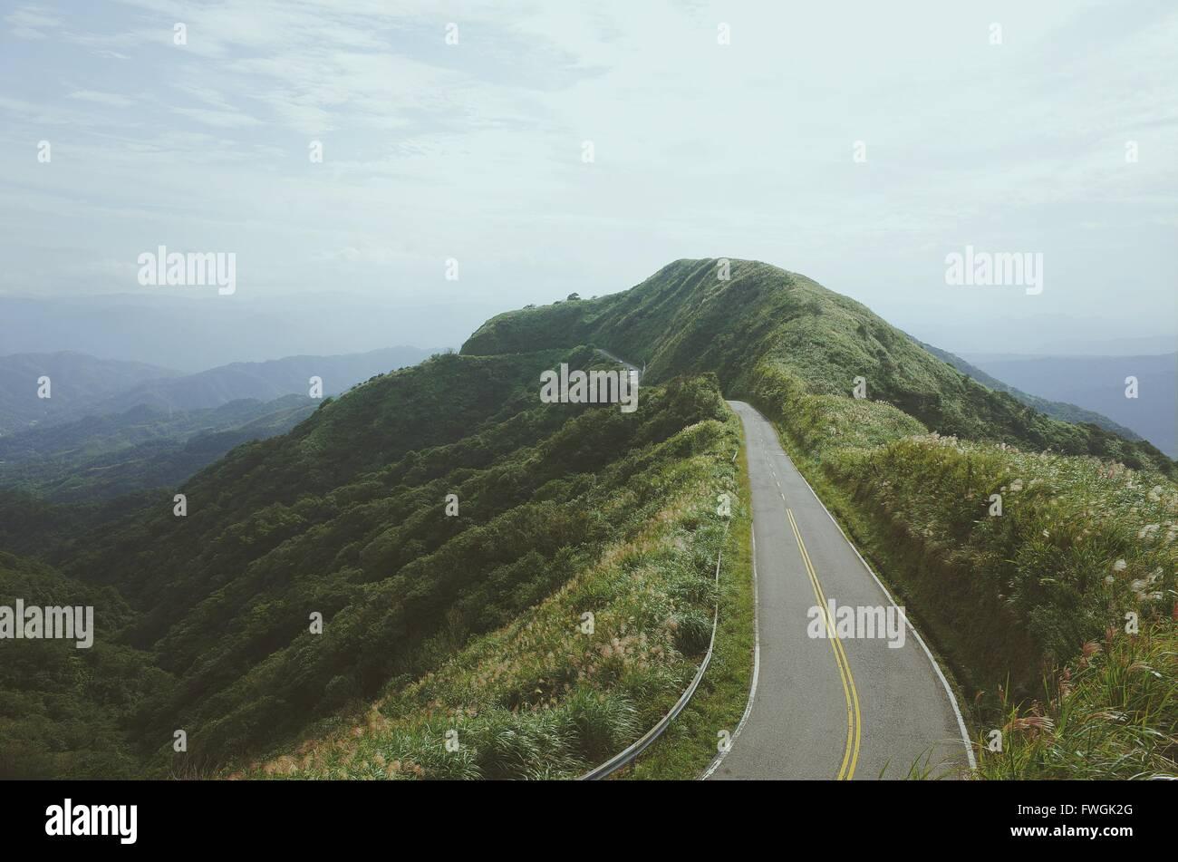 Strada di campagna contro il cielo nuvoloso Immagini Stock