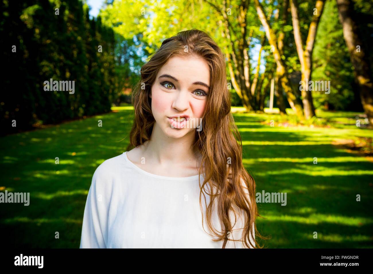Una giovane e bella ragazza in posa per una moda stile ritratto all'aperto presso un parco con illuminazione Immagini Stock