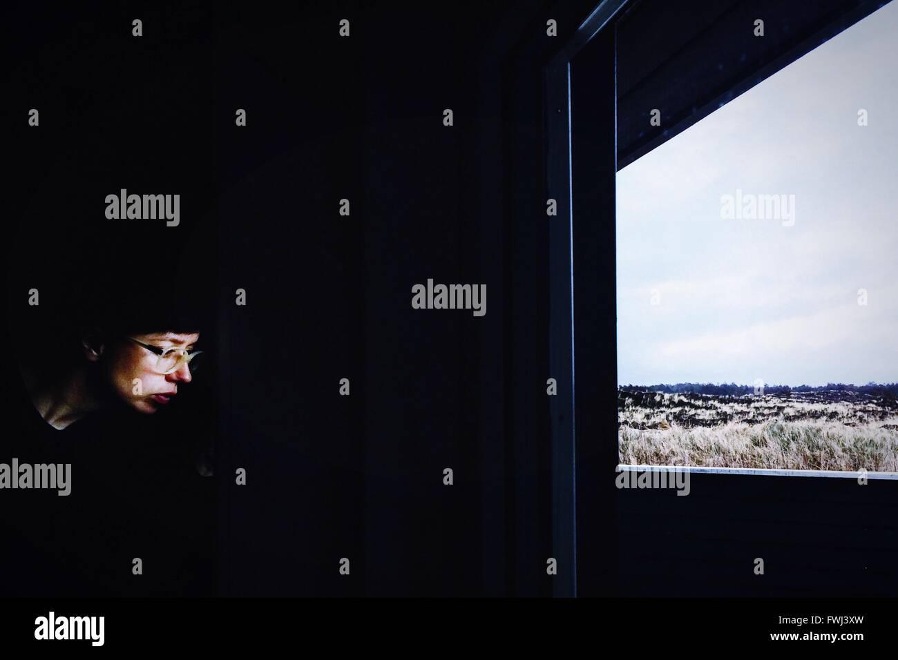 Premurosa donna che indossa occhiali seduto davanti alla finestra di casa Immagini Stock