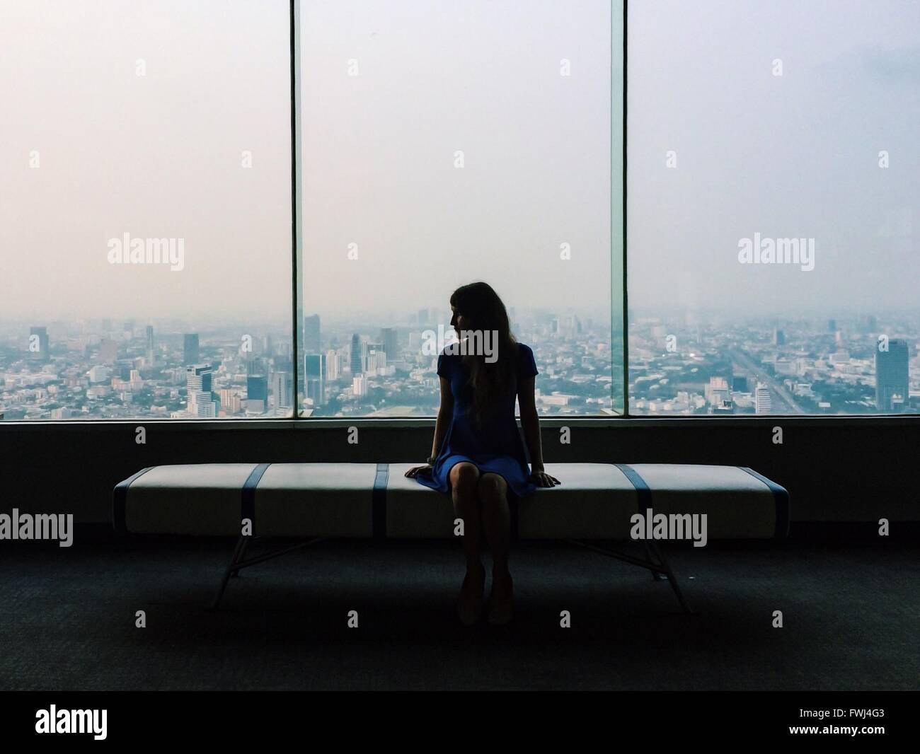Giovane donna in vestito blu seduto sul sedile contro il vetro della finestra in città Immagini Stock