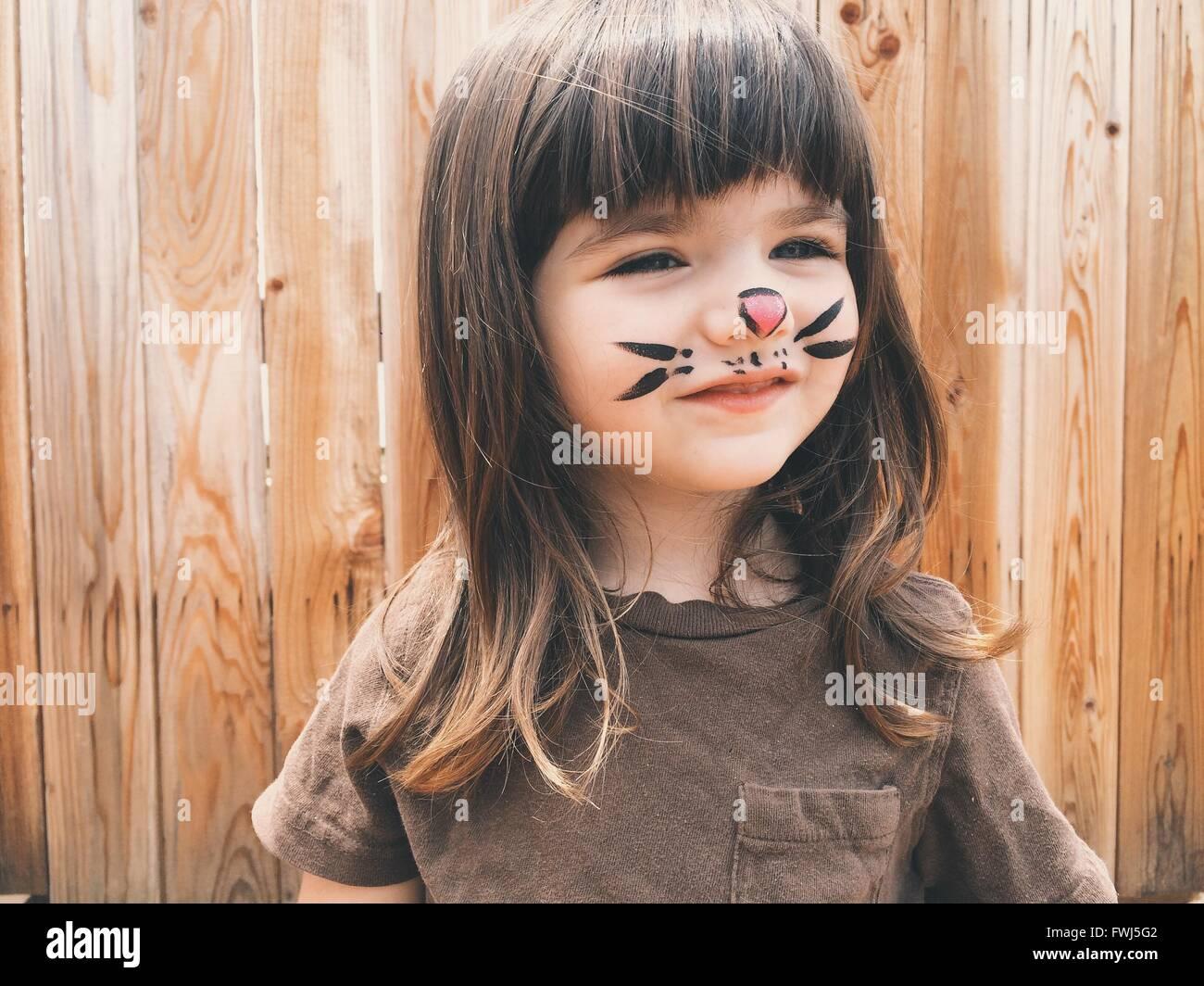 Close-Up di sorridente ragazza carina con dipinto sul volto all'aperto permanente Immagini Stock