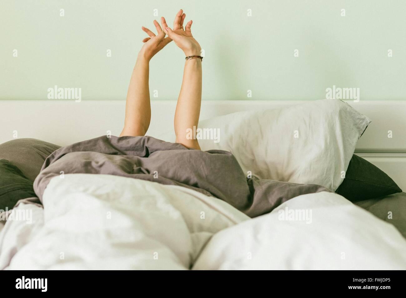Donna con le braccia sollevate durante i momenti di relax sul letto di casa Foto Stock