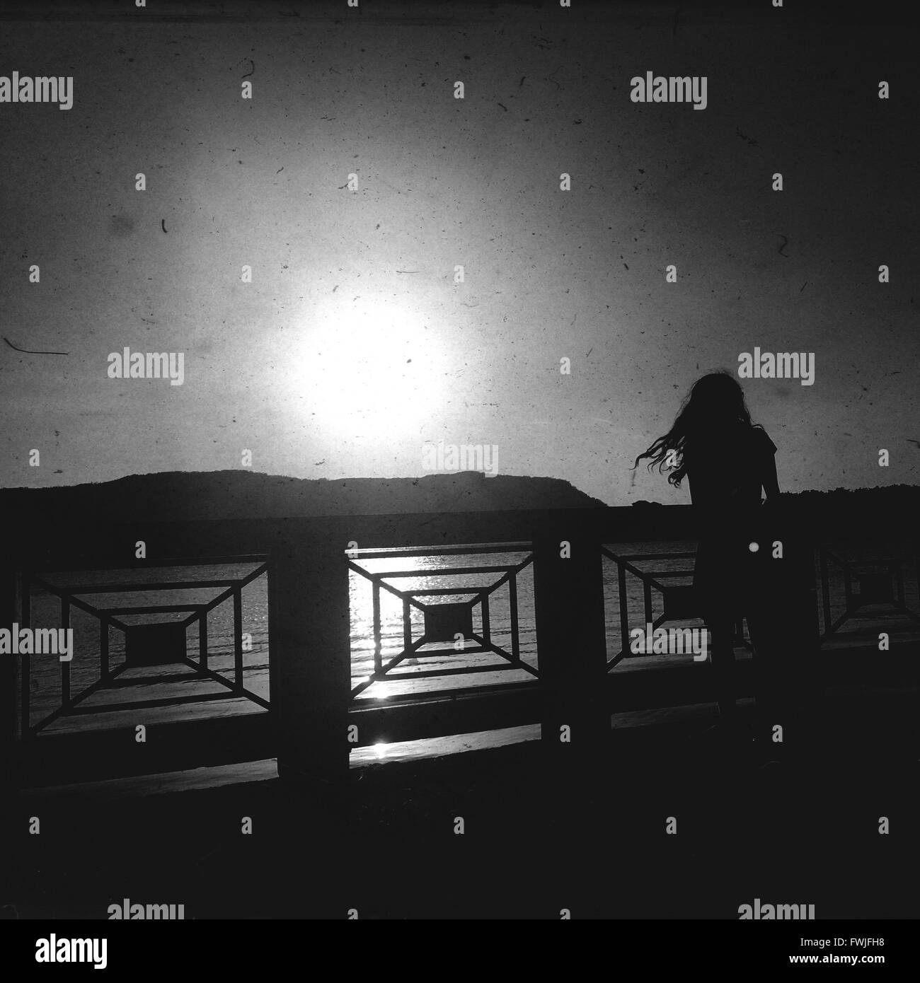 Silhouette permanente sulla passerella sul fiume contro il cielo luminoso Immagini Stock