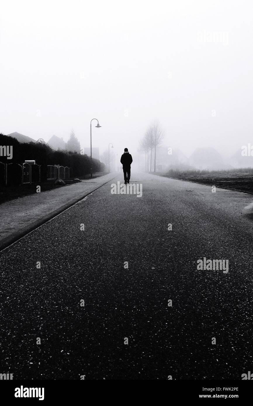 Silhouette chi cammina sulla strada Immagini Stock