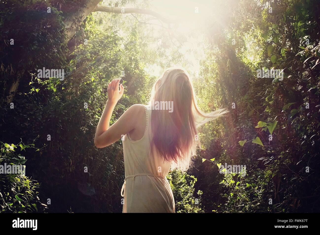 Vista posteriore di una donna in piedi contro alberi Immagini Stock