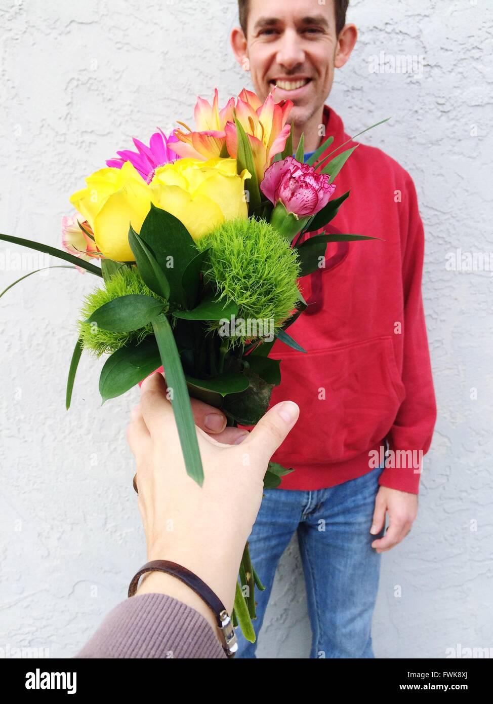 Immagine ritagliata della donna bouquet di ricezione da ragazzo contro la parete Immagini Stock