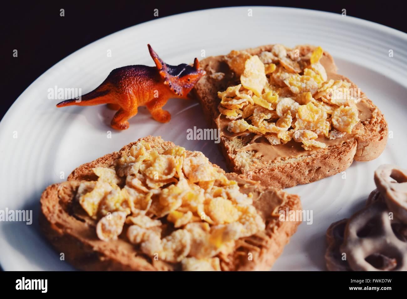 Dinosauro giocattolo con la colazione servita nella piastra Immagini Stock