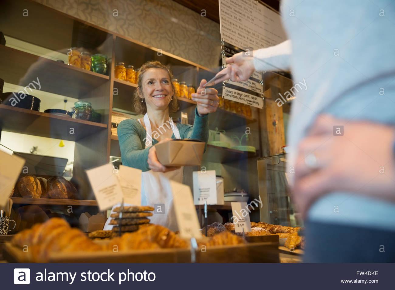 Il cliente di pagare il proprietario da forno con carta di credito Immagini Stock