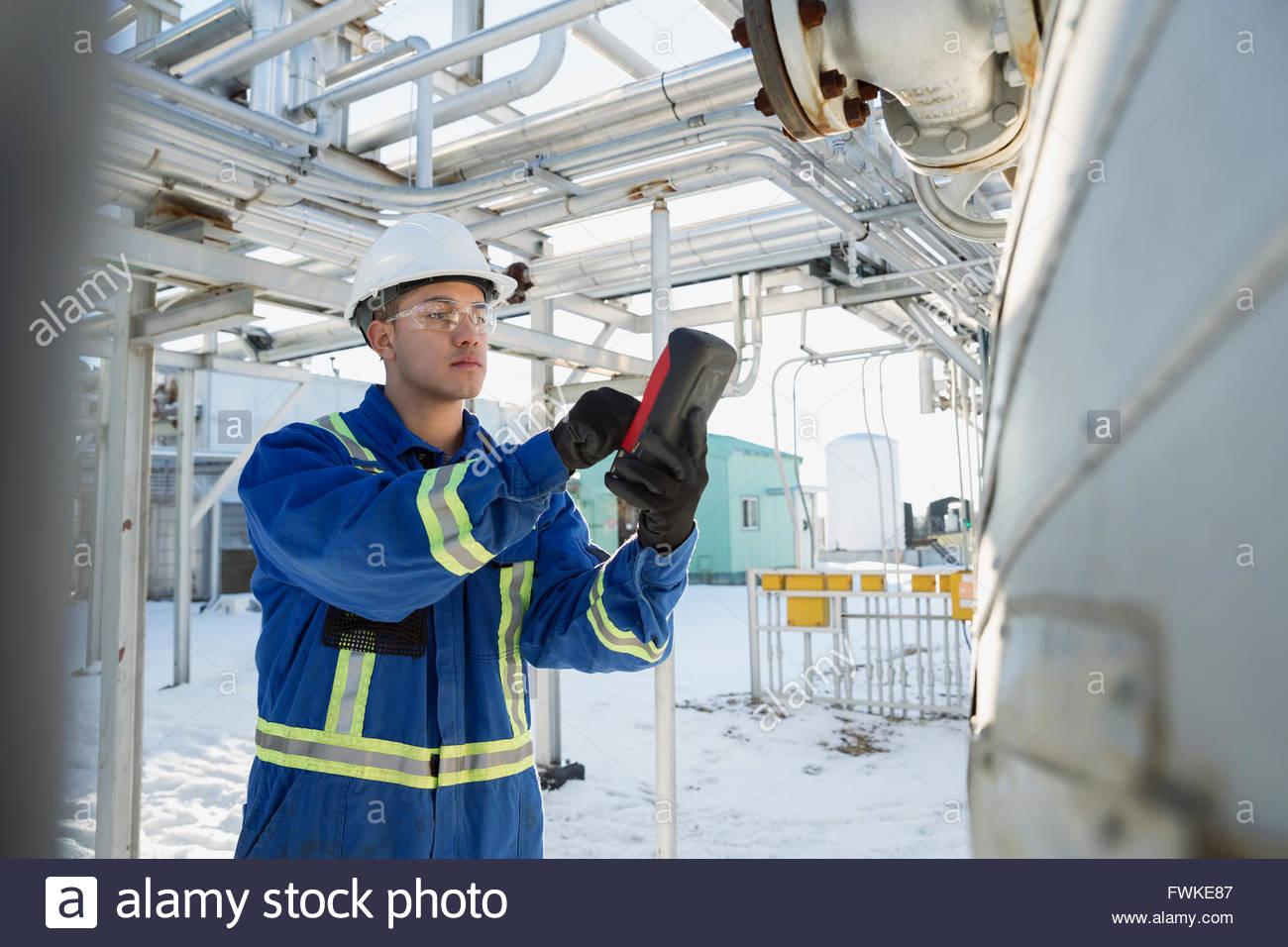 Lavoratore di sesso maschile con il dispositivo wireless in impianto a gas Immagini Stock