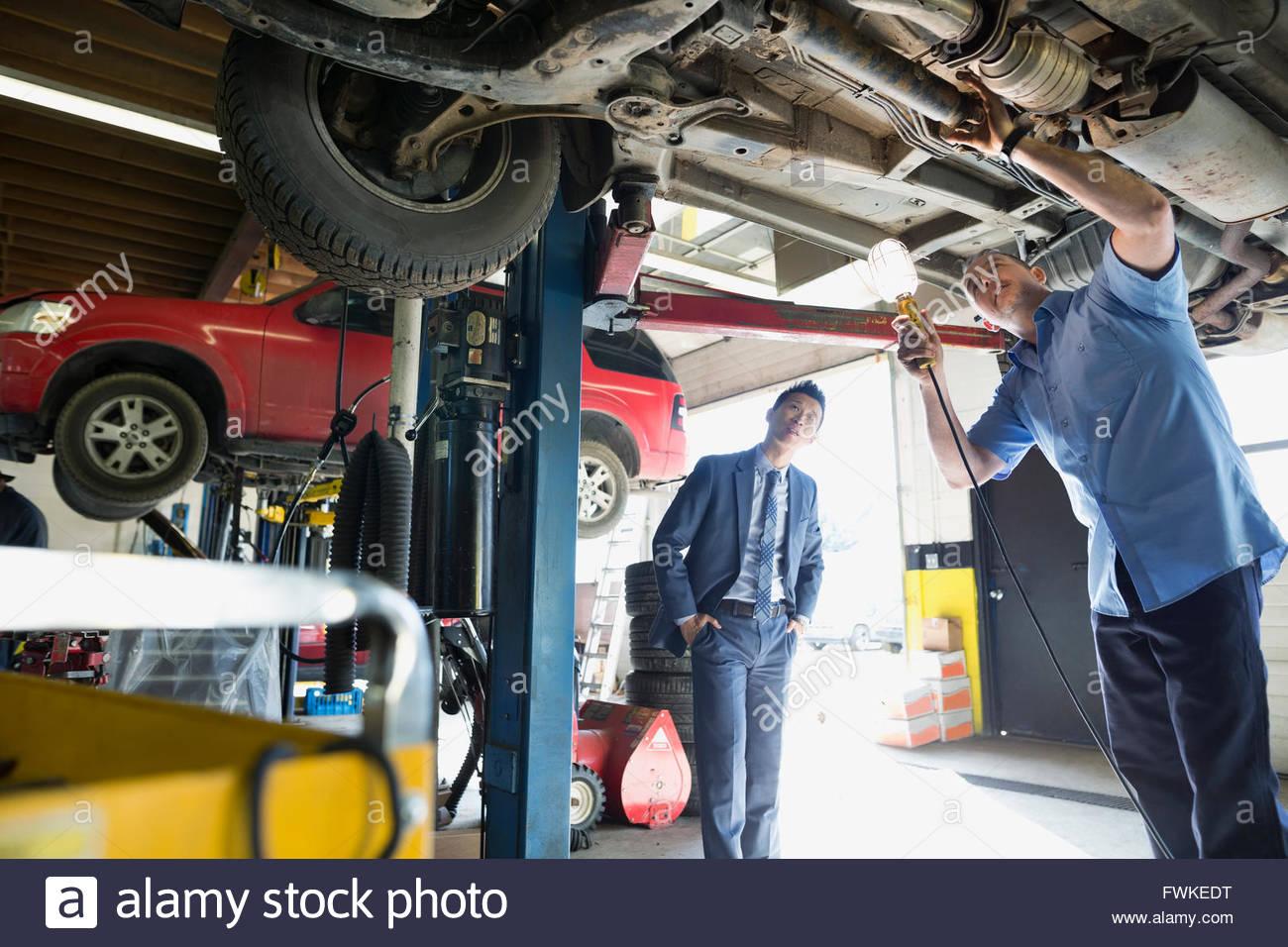 Meccanico e il cliente sotto auto auto officina di riparazione Immagini Stock