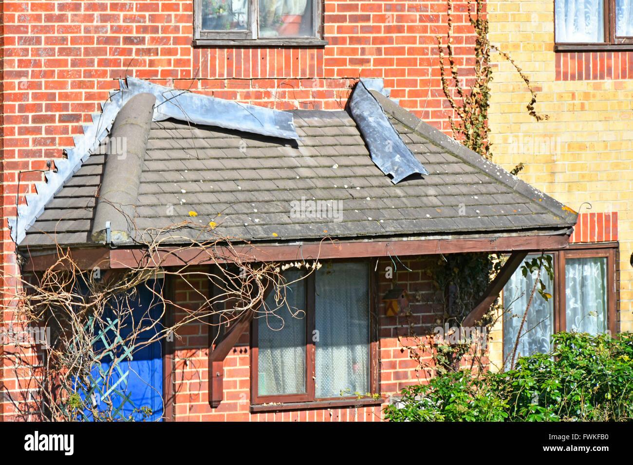 Il filo difettoso lampeggiante a riscontro della casa in pendenza Tetto portico e un muro di mattoni non è Immagini Stock