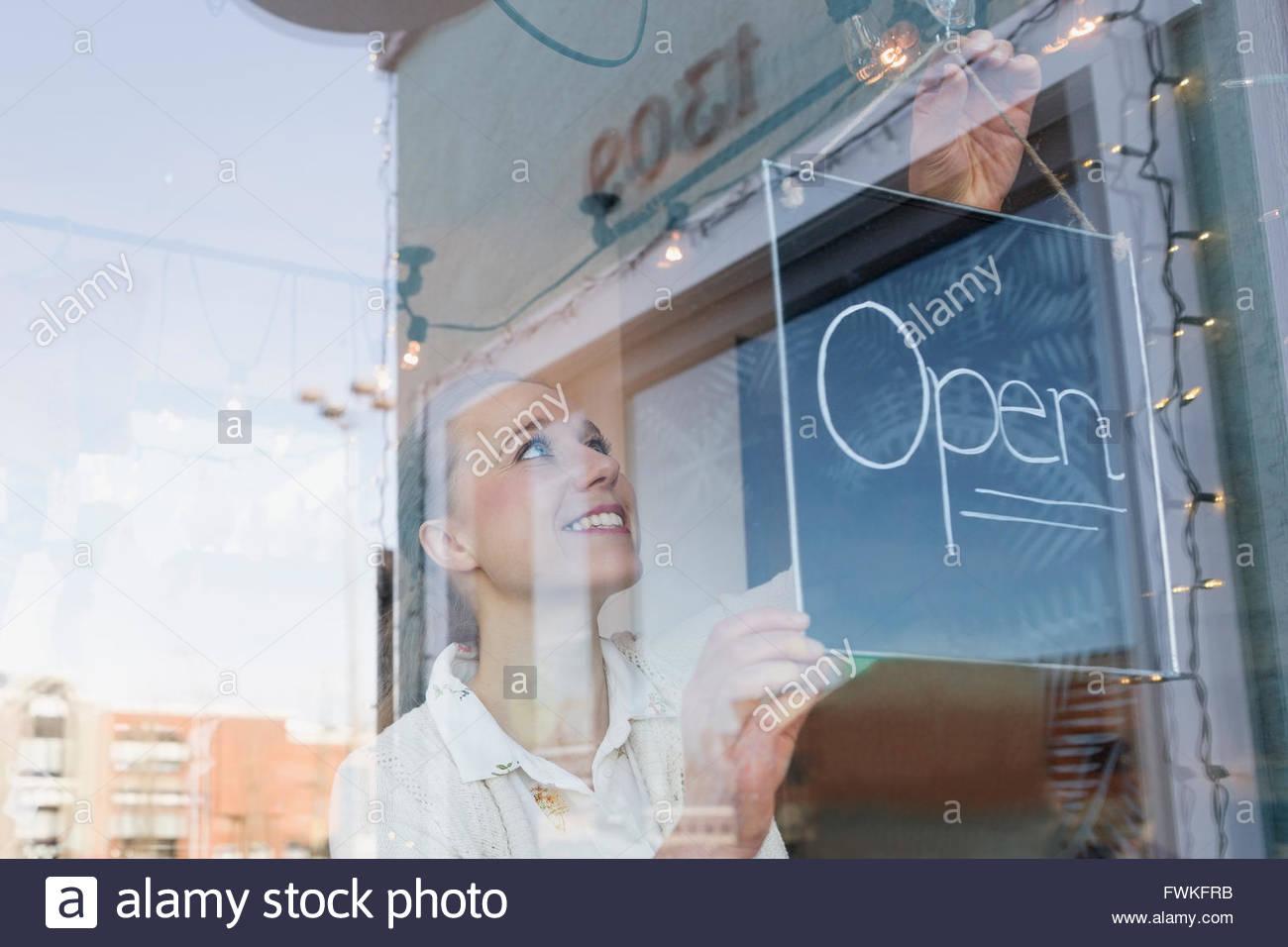 Sorridente proprietario di un negozio di tornitura segno aperto in corrispondenza della finestra Immagini Stock
