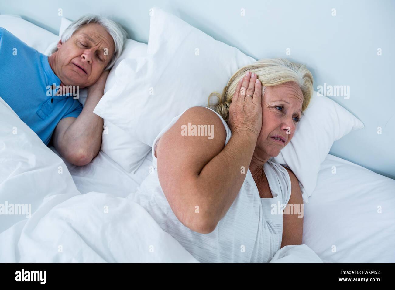 Senior donna bloccando le orecchie mentre l uomo il russamento Immagini Stock