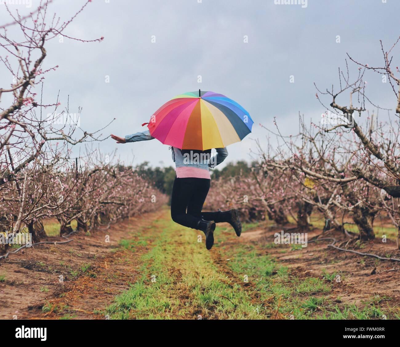 Donna con ombrello coloratissimo saltando su campo erboso contro Sky Immagini Stock