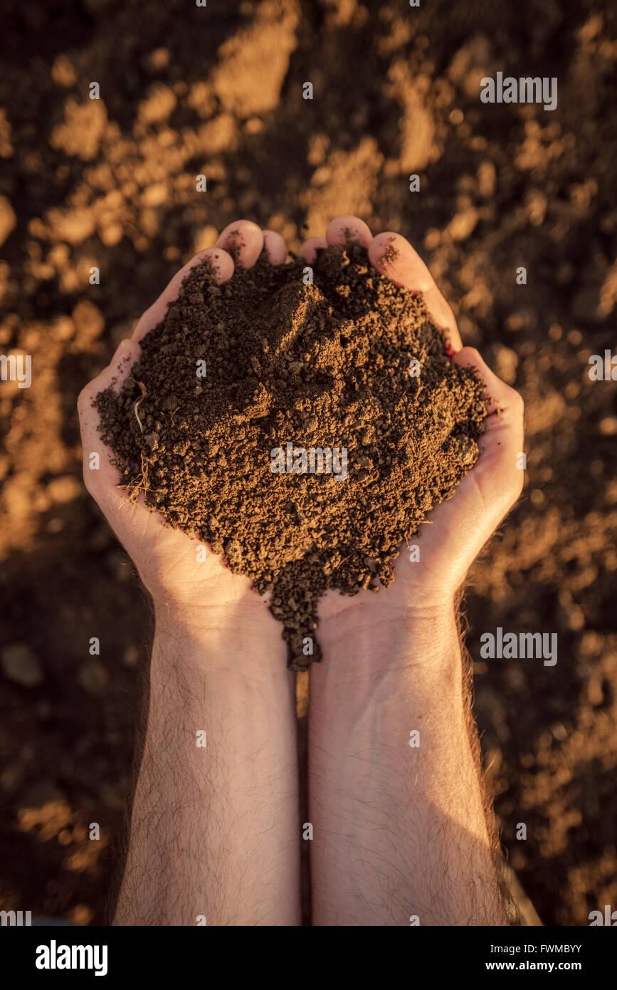 Seminativi terreno nelle mani di un agricoltore responsabile, caucasico maschio agricoltore pila di contenimento Immagini Stock