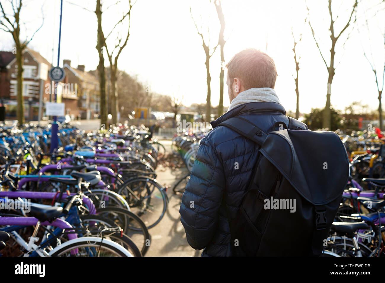 Vista posteriore dell'uomo lasciando Bike nel Parco del ciclo a Rail Station Immagini Stock