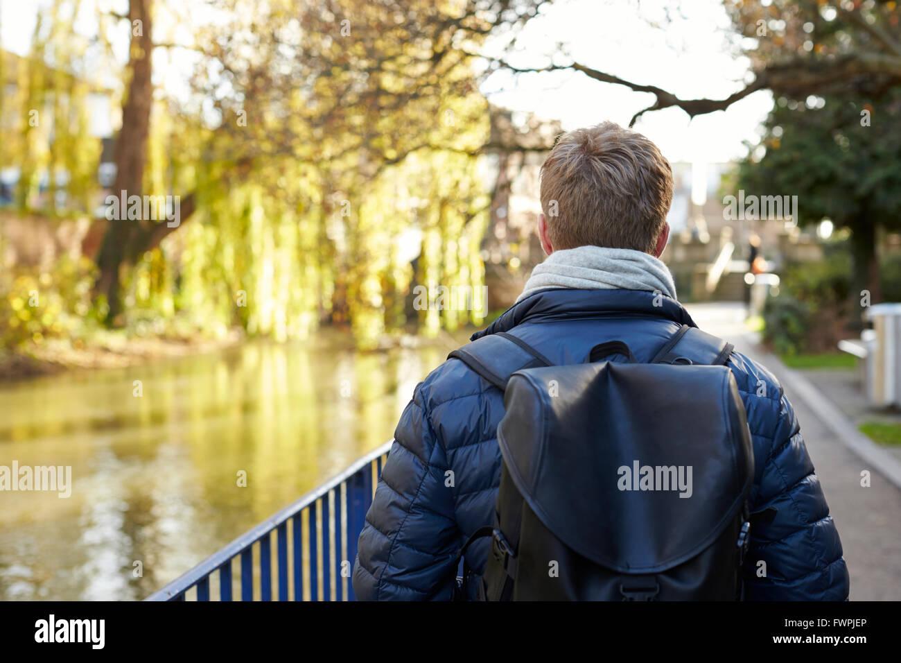 Vista posteriore del giovane uomo a piedi dal fiume in città Immagini Stock