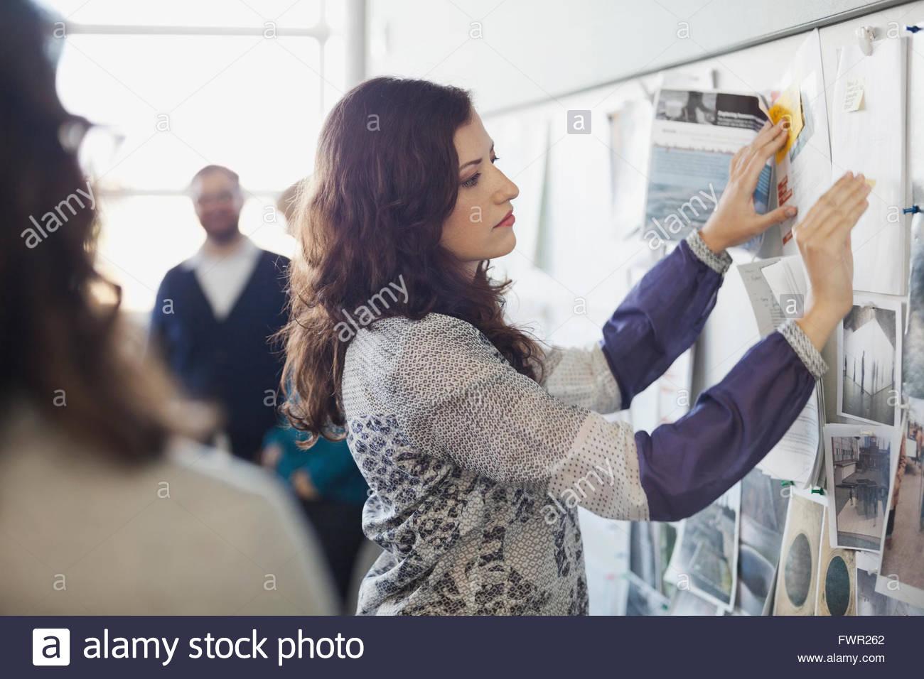 Imprenditrice pinning note sulla bacheca Immagini Stock