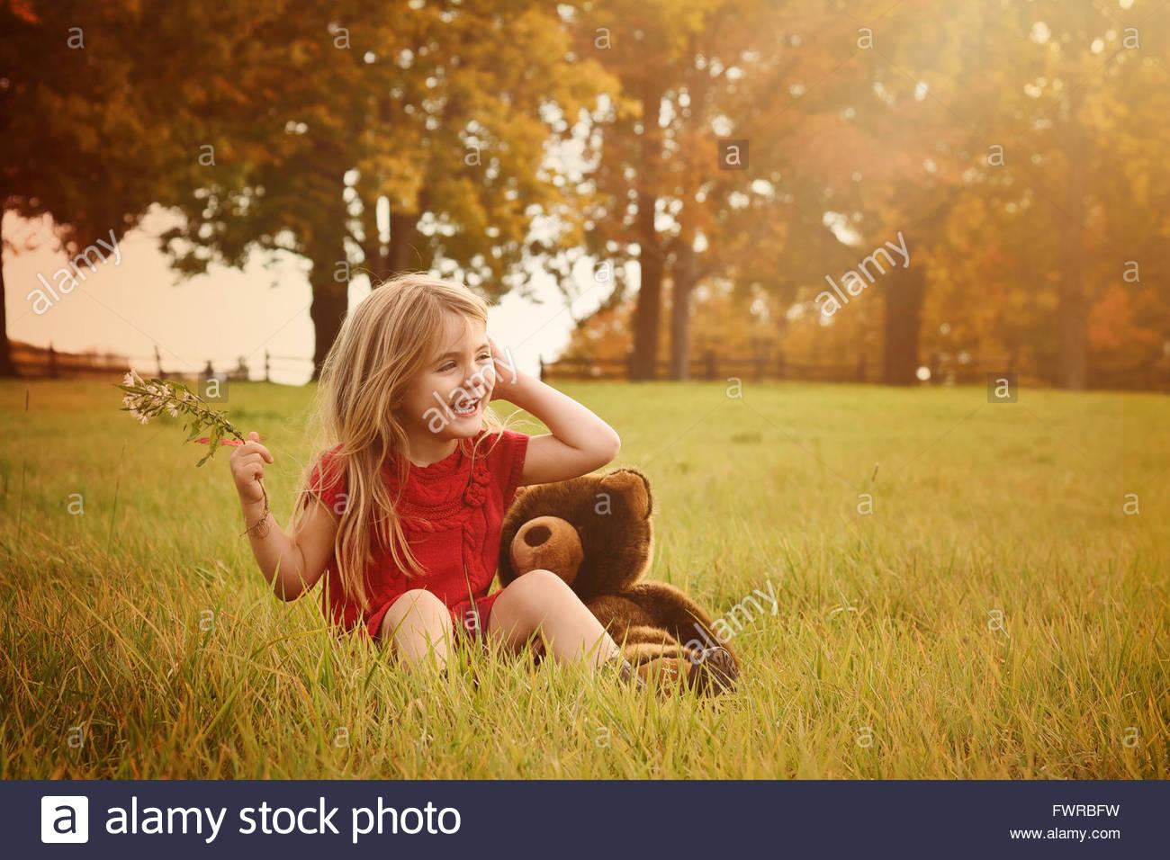 La bambina è seduta al di fuori del paese con erba verde e sole per una felicità o concetto Natura. Immagini Stock