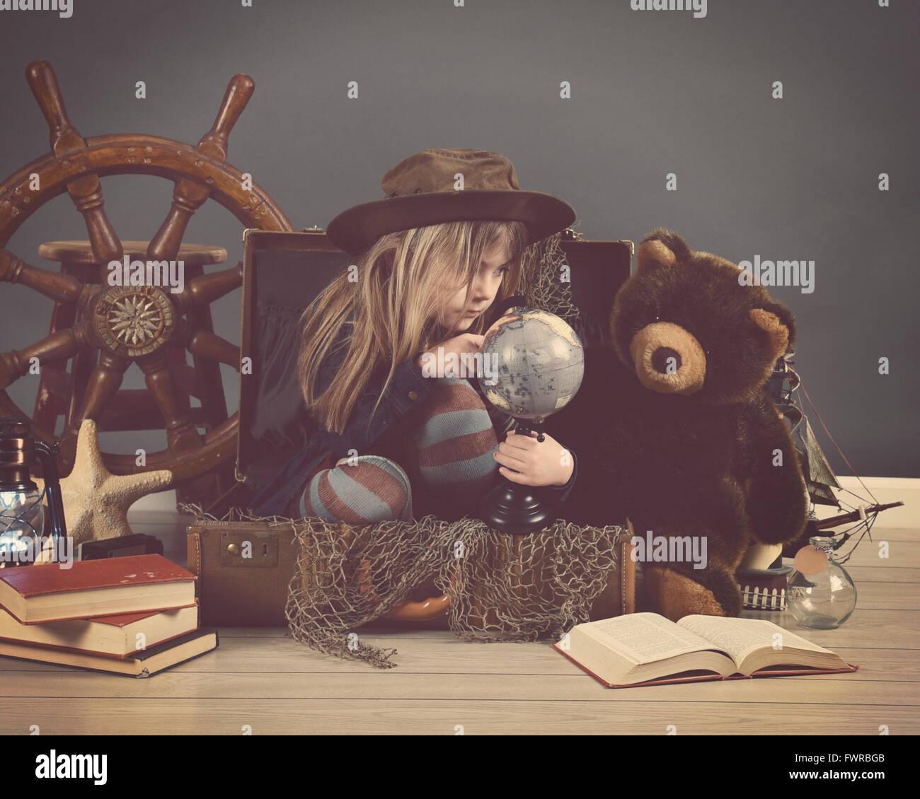 Un bambino piccolo che è seduto in una valigia viaggio guardando un globo con puntelli del mare per un' Immagini Stock