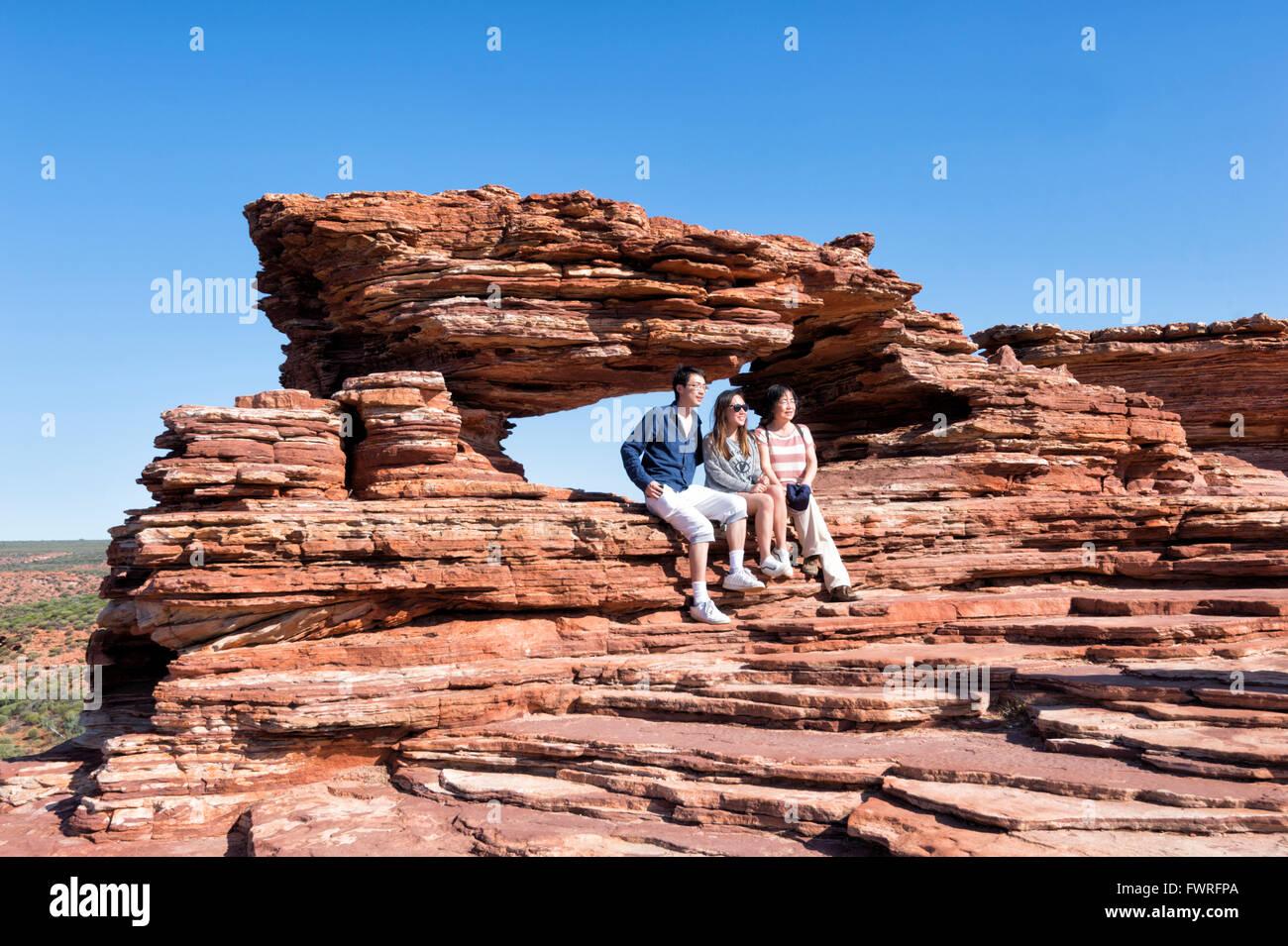 I turisti che posano per una foto alla natura della finestra, Kalbarri National Park, Australia occidentale, Australia Immagini Stock