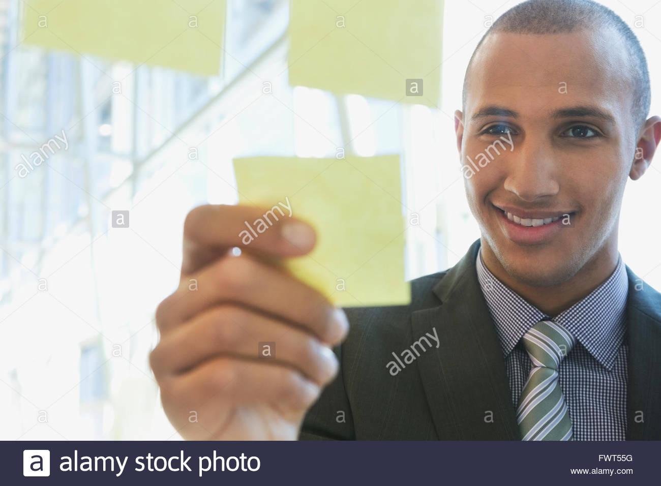 Giovane imprenditore mettendo una nota adesiva sul vetro Immagini Stock