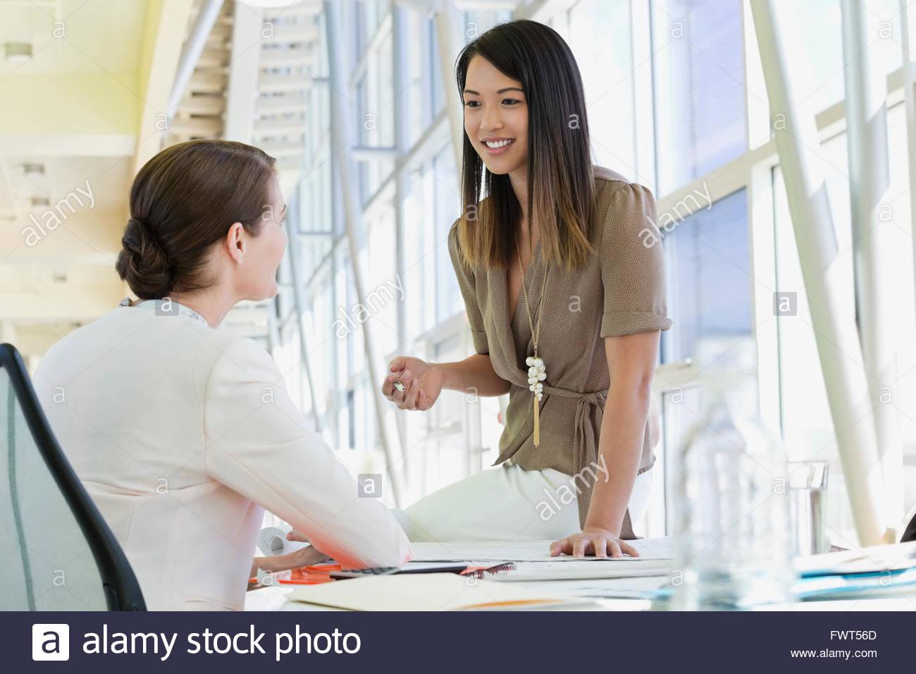 Femmina di colleghi di lavoro più di parlare di scrivania in sala conferenze Immagini Stock