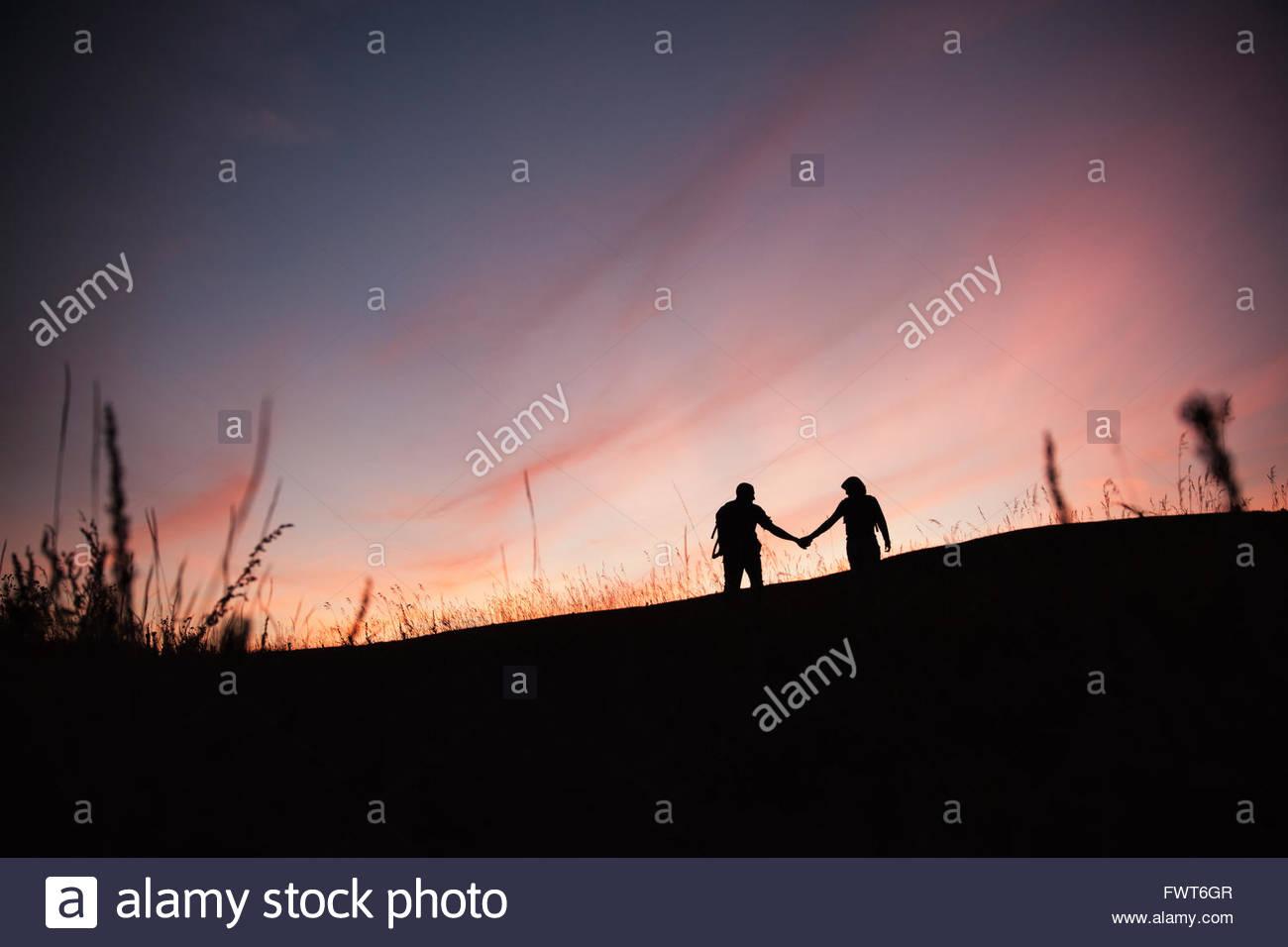 Silhouette di giovane tenendo le mani all'esterno. Immagini Stock