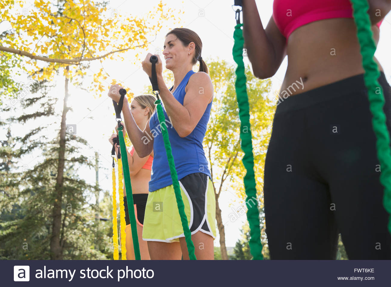 Le donne che utilizzano bande di resistenza all'aperto classe fitness. Immagini Stock