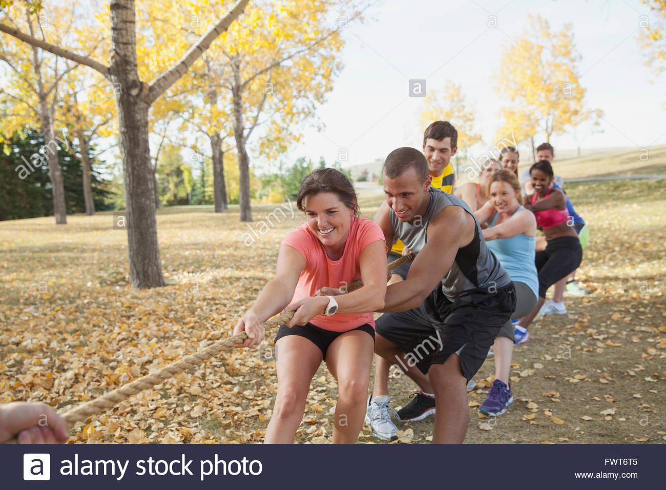 Lezione di fitness facendo rimorchiatore di guerra all'esterno. Immagini Stock