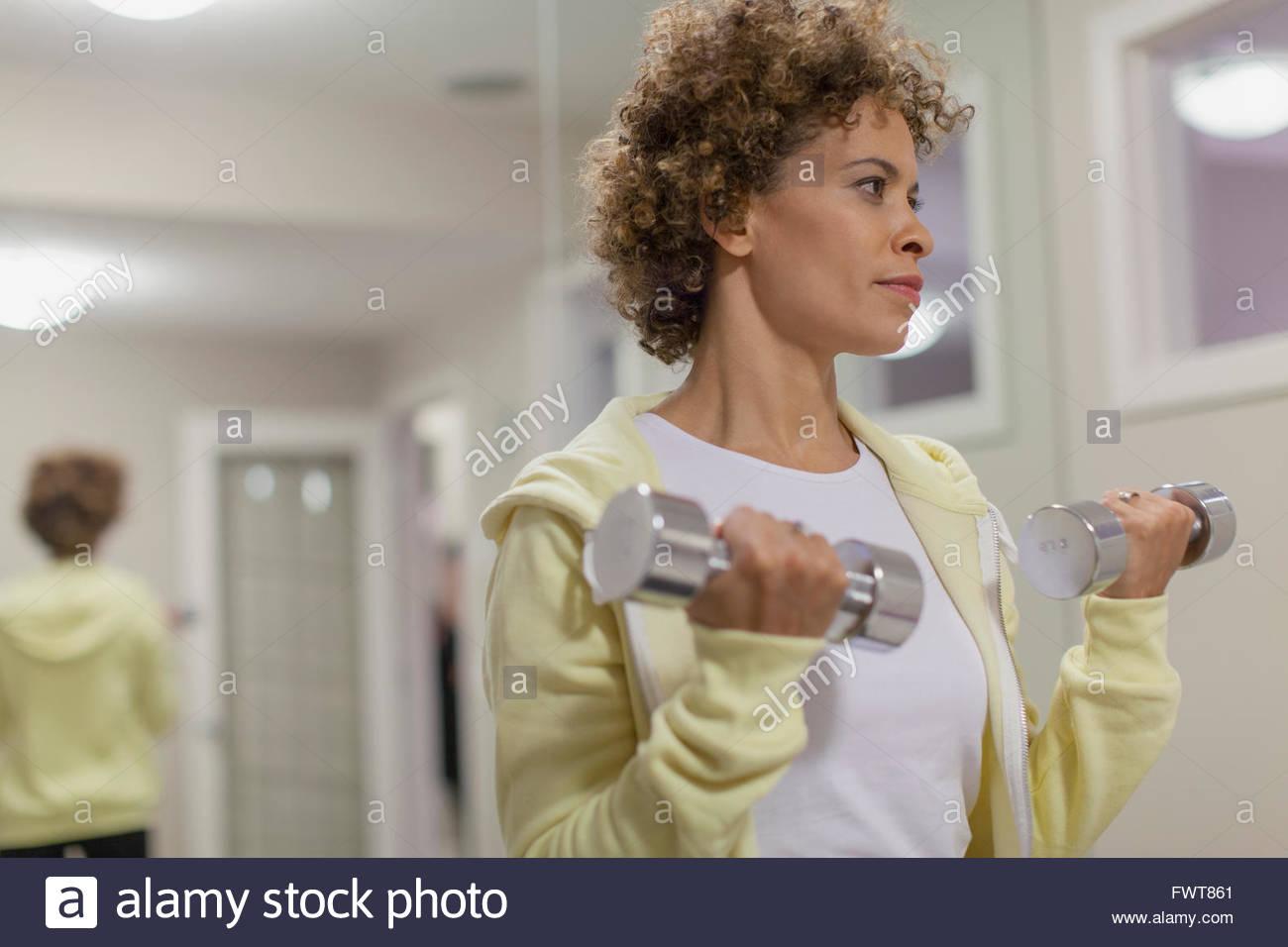 Donna che utilizza i pesi per allenamento. Immagini Stock
