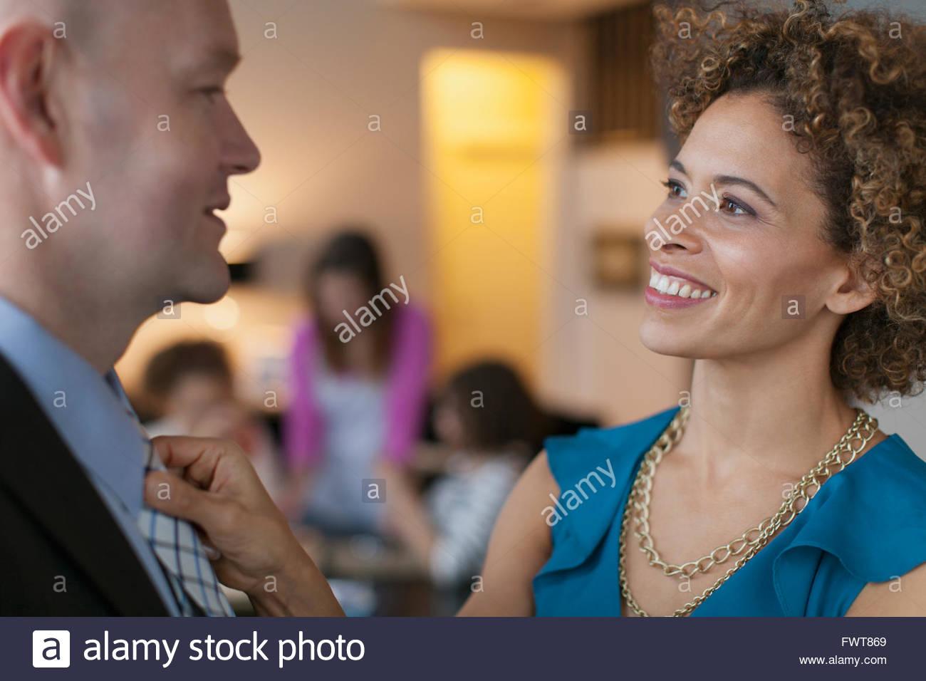Regolazione della moglie mariti cravattina prima di andare fuori. Immagini Stock