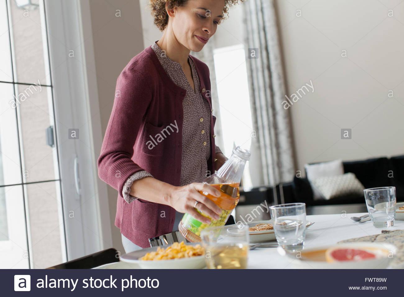 Donna succo di versamento al tavolo per la colazione. Immagini Stock
