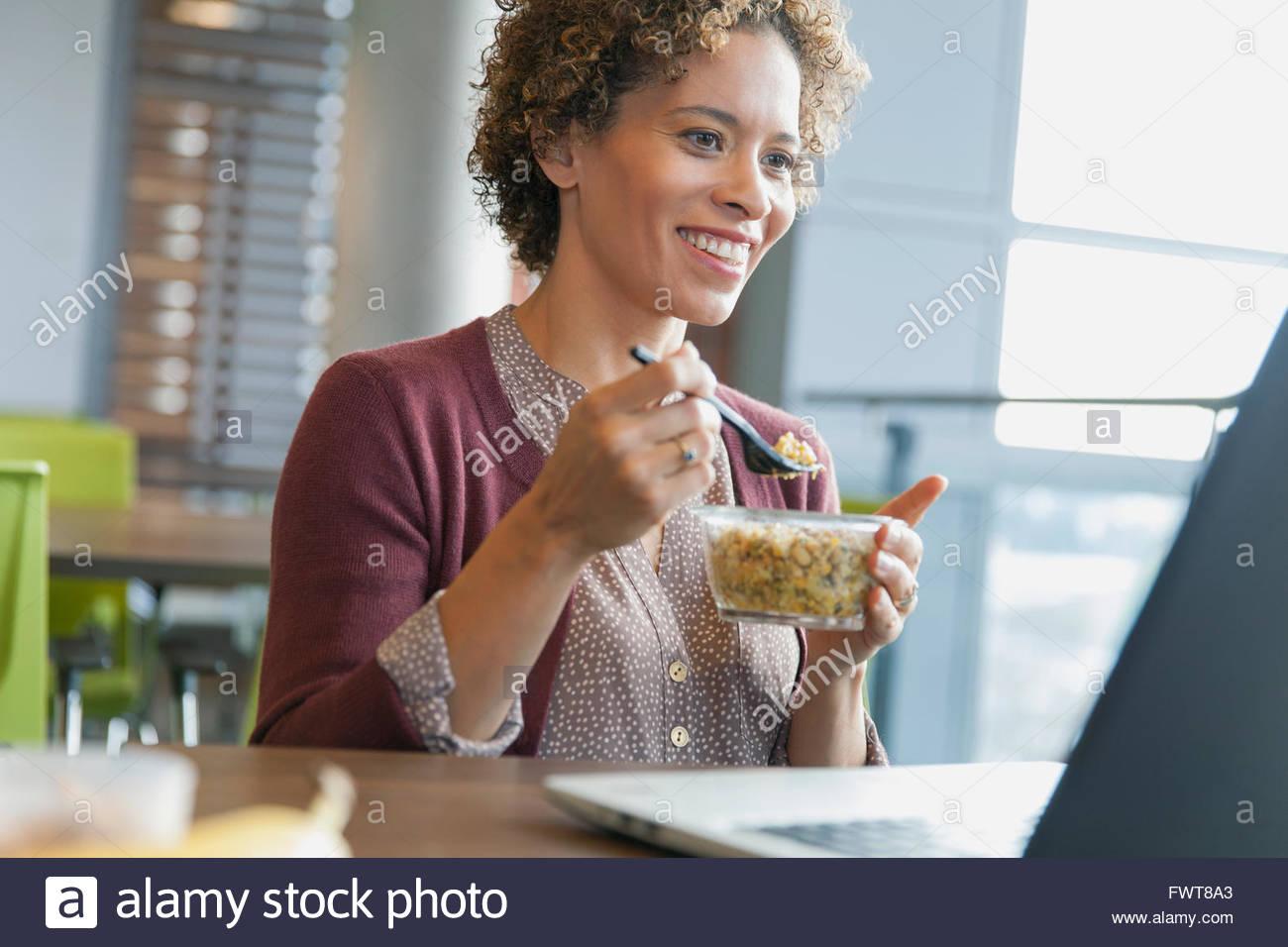 Donna sorridente come lei snack presso il suo computer portatile. Immagini Stock