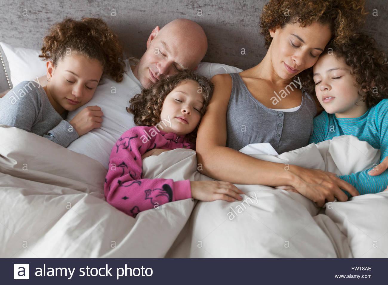 Famiglia di cinque persone dormono insieme pacificamente. Immagini Stock