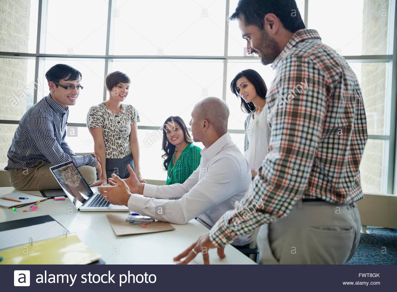 Team aziende aventi una conversazione attorno a scrivania Immagini Stock