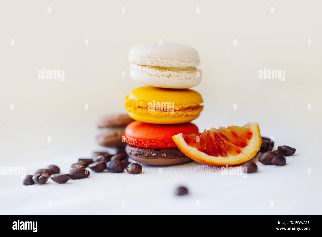 Amaretti colorati torre close-up su sfondo nero. Il gusto del caffè e rosso arancio, grano, frutta Immagini Stock