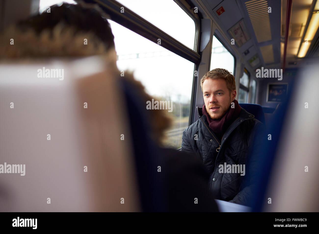 Due uomini seduti nella carrozza del treno e parlare Immagini Stock
