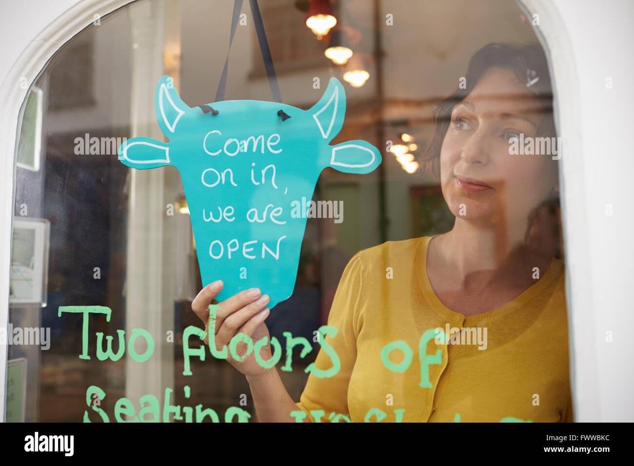 Proprietaria del Coffee Shop girando segno aperto Immagini Stock