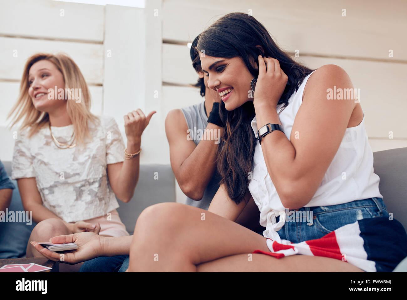 Ritratto di giovani amici appendere fuori a giocare a carte con donna ascoltando un segreto da un suo fidanzato. Immagini Stock
