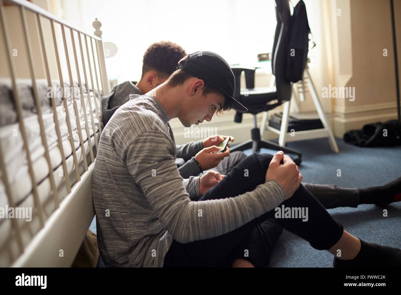 Due gli studenti maschi in camera da letto controllare i messaggi su telefoni cellulari Immagini Stock
