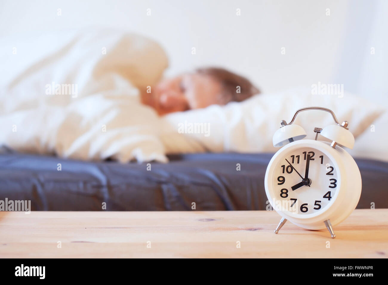 Svegliarsi la mattina con sveglia, persona che dormiva nel letto Foto Stock