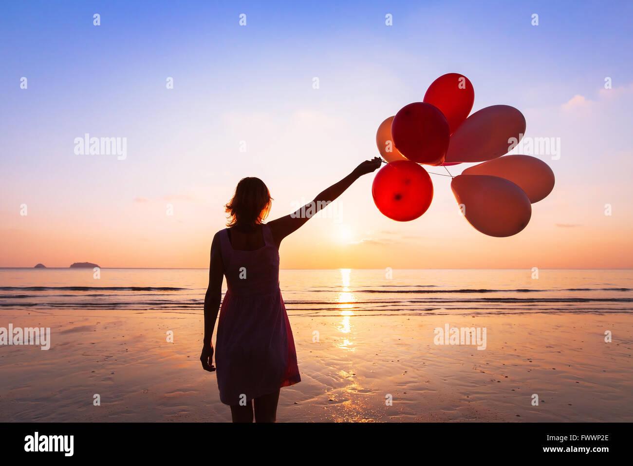 Fantasia e creatività, ragazza con palloncini multicolori al tramonto con copyspace, ispirazione concept Immagini Stock