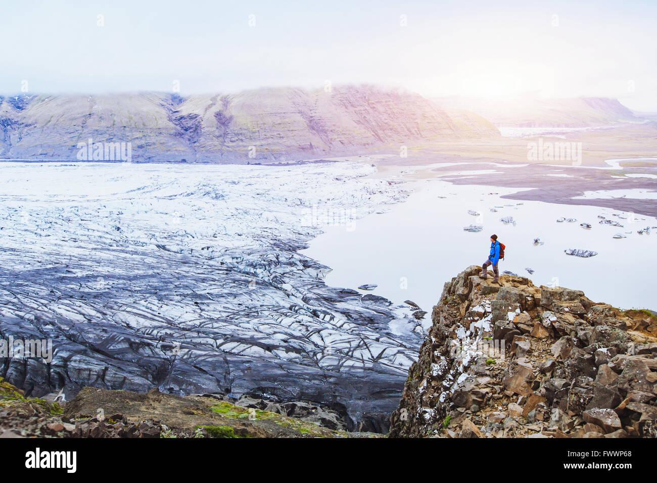 Escursionismo in inverno, backpacker godendo di paesaggio panoramico del ghiacciaio in Islanda al tramonto nel parco Immagini Stock