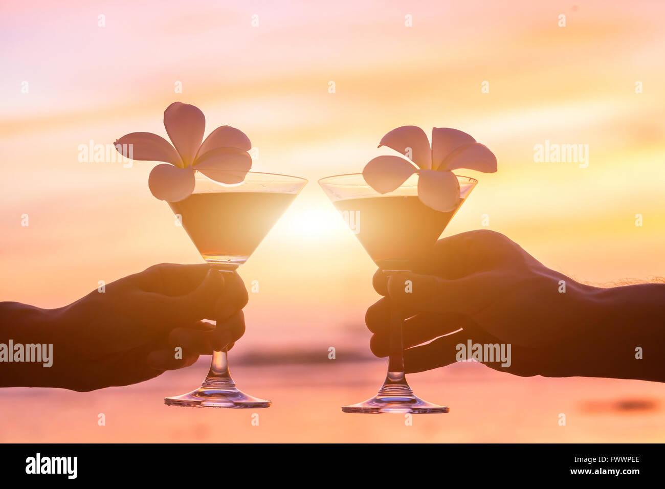 Cocktail tropicale sulla spiaggia e in un paio di mani con gli occhiali Immagini Stock